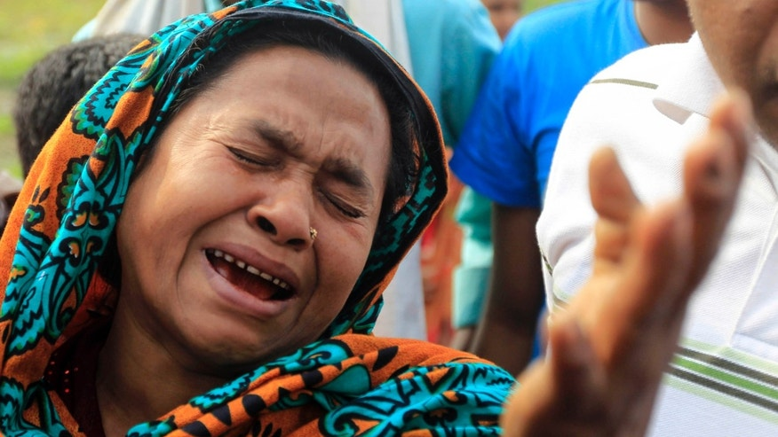 A Bangladeshi woman mourns victims of a ferry that capsized on the banks of the Meghna River at at Munshiganj, 32 kilometers (20 miles) south of Dhaka, Bangladesh, Friday, Feb. 8, 2013. The passenger ferry capsized Friday after colliding with another ship on a river in central Bangladesh, dumping as many as 100 people into the water, officials and witnesses said. (AP Photo/A.M. Ahad)