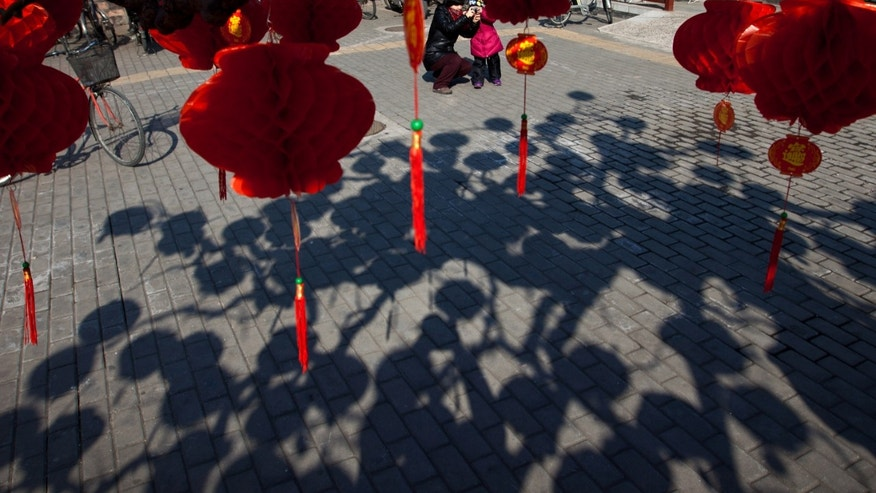 A Chinese woman helps her child to snap pictures near a tree decorated with red lanterns ahead of Chinese New Year celebrations at Ditan Park in Beijing Friday, Feb. 8, 2013. Chinese will celebrate the Lunar New Year on Feb. 10 this year which marks the Year of Snake. (AP Photo/Andy Wong)