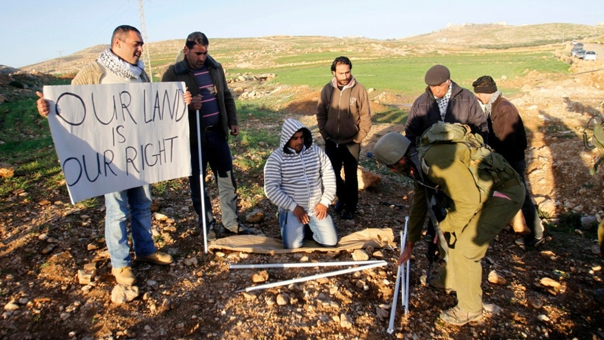 Israeli soldier picks up parts of a tent previously set up by Palestinian activists in Yatta, south of the West Bank city of Hebron, Saturday, Feb. 9, 2013. Palestinian activists set up a tent village to protest the settlement building in the area. (AP Photo/Nasser Shiyoukhi)