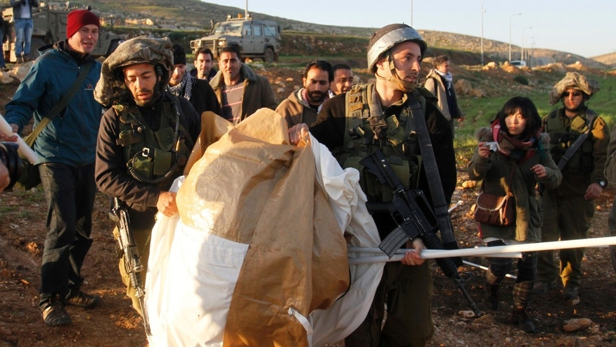 Israeli soldiers carry parts of a tent previously set up by Palestinian activists in Yatta, south of the West Bank city of Hebron, Saturday, Feb. 9, 2013. Palestinian activists set up a tent village to protest the settlement building in the area. (AP Photo/Nasser Shiyoukhi)