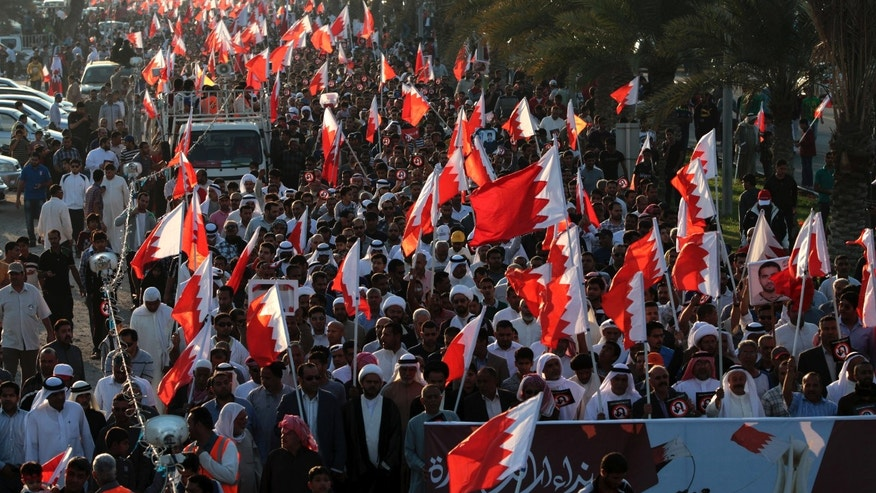 Bahraini anti-government protesters wave national flags and carry images of people who are jailed or have died in the past two years of a pro-democracy uprising during a march in Diraz, Bahrain on Feb. 6. (AP Photo/Hasan Jamali)