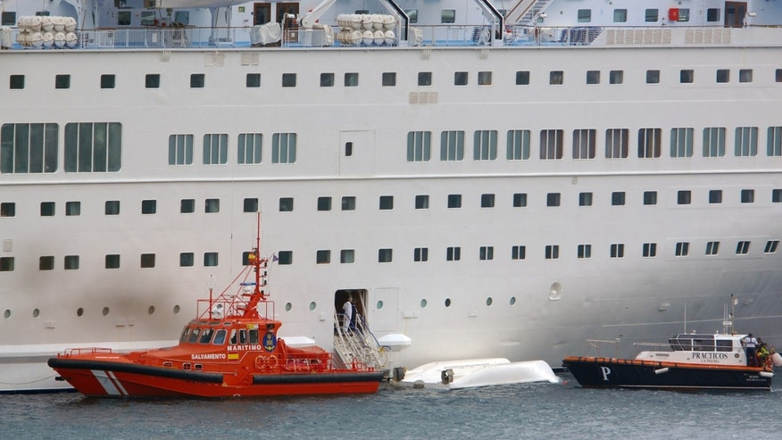 An orange rescue boat docks by a capsized lifeboat from the British-operated cruise ship Thomson Majesty in Santa Cruz port of the Canary Island of La Palma, Spain, Sunday Feb. 10, 2013. A lifeboat from the Thomson Majesty fell into the sea at port in Spainâs Canary Islands, killing five people and injuring three others Sunday, officials said. Rescue personnel were called to the dockside after a lifeboat with occupants had fallen overboard from a cruise ship. Spanish national broadcaster RTVE said an emergency training drill was taking place at the time of the accident. (AP Photo/Manuel Gonzalez)