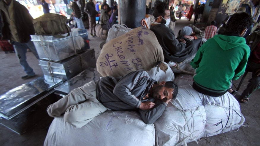 Kashmiri passengers rest on luggage as they wait for the Jammu-Srinagar bus services, temporarily suspended due to curfew in Srinagar,  at a bus stand in Jammu, India, Saturday, Feb. 9,2013. A Kashmiri man Mohammed Afzal Guru, convicted in the 2001 attack on India's Parliament, has been hanged in an Indian prison, a senior Indian Home Ministry official said Saturday. On Saturday morning thousands of police and paramilitary troops had fanned out across Indian Kashmir anticipating that protests and violence might follow news of the execution. (AP Photo/Channi Anand)