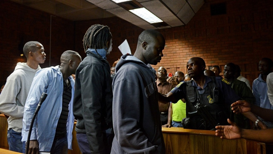 Unidentified suspects are led out of court after appearing in Pretoria, South Africa, Thursday, Feb. 7, 2013. Nineteen alleged members of a Congolese rebel group  including one U.S. citizen  sought help in their effort to overthrow Congolese President Joseph Kabila, offering mining rights in their resource-rich country in exchange for weapons and training, a prosecutor said Thursday. (AP Photo)