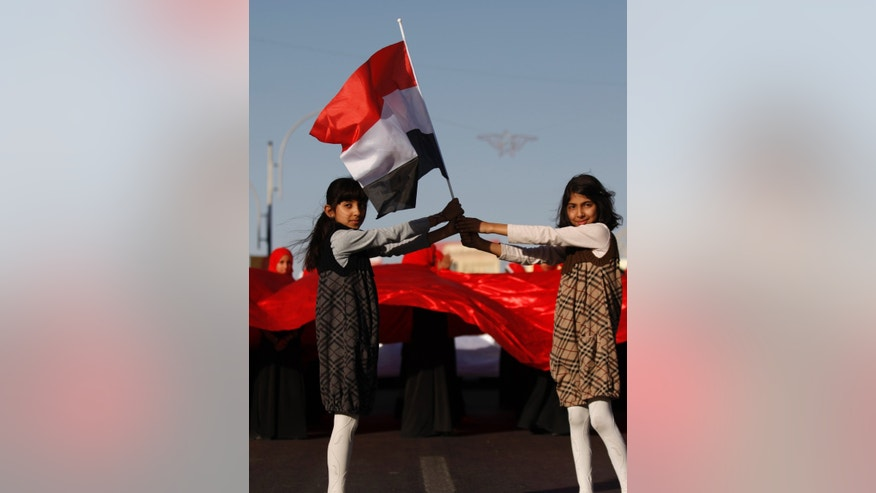 Yemeni girls hold their national flag during a parade marking the second anniversary of the revolution in Sanaa, Yemen, Monday, Feb. 11, 2013. The 2011 Yemeni Revolution was as an extension of the broader Arab Spring which has toppled four authoritarian leaders to date. Yemenis were able to create a unique revolution, their struggle came peacefully, unarmed, and lead by women and youth. (AP Photo/Hani Mohammed)