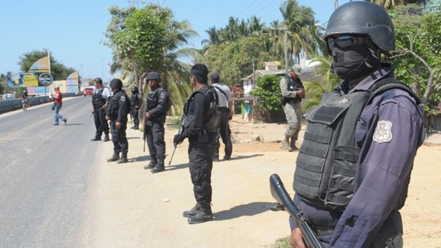 State police stand at a roadblock due to stepped up security after masked armed men broke into a beach home, raping six Spanish tourists who had rented the house in Acapulco, Mexico, Tuesday Feb. 5, 2013.