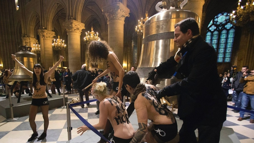 Activists of the Women's Movement FEMEN,  are confronted by security guards as they stand by one of the bells ordered for the cathedral's 850th birthday, in Notre Dame Cathedral, Paris,  in protest against Pope Benedict XVI who announced his resignation yesterday,  in Paris, Tuesday, Feb. 12, 2013.  (AP Photo/Michel Euler)