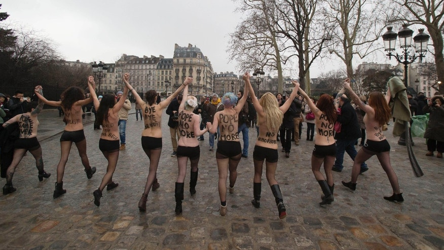Activists of the Women's Movement FEMEN, protest against the Pope Benedict XVI who announced his resignation yesterday,  in Notre Dame Cathedral, Paris, Tuesday, Feb. 12, 2013.  (AP Photo/Michel Euler)