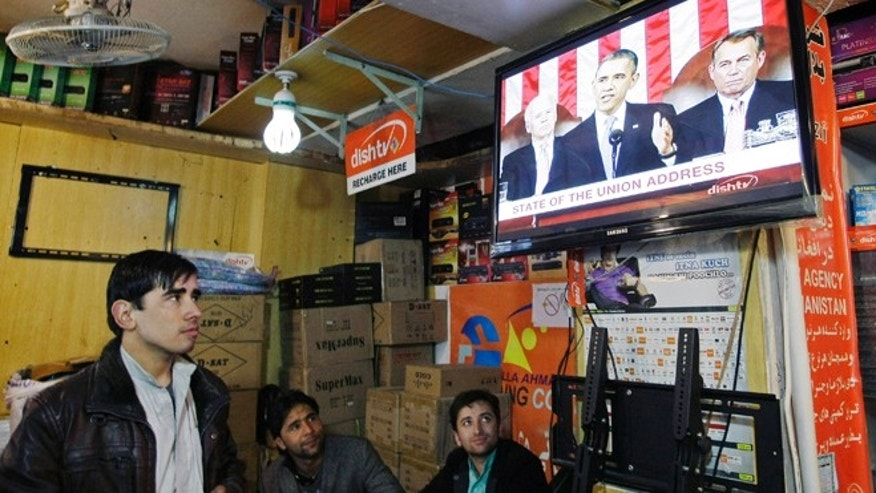 Feb. 13, 2013: Afghan men watch a television news report on U.S. President Barack Obama's State of the Union address in Kabul, Afghanistan Wednesday.