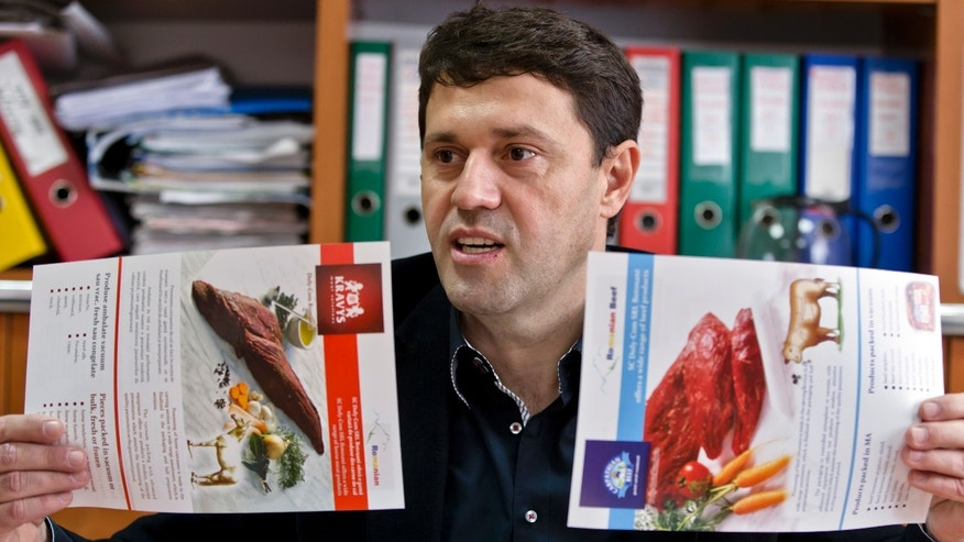 Iulian Cazacut, he general manager of the Doly-Com abattoir, one of the two units checked by Romanian authorities in the horse meat scandal, shows product specification sheets for horse meat and beef, in the village of Roma, northern Romania, Tuesday, Feb. 12, 2013. On Monday, Romanian officials scrambled to defend two plants implicated in the scandal, saying the meat was properly declared and any fraud was committed elsewhere. (AP Photo/Vadim Ghirda)