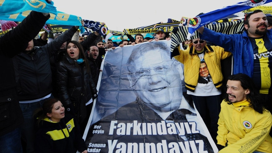 "FILE - In this Monday, Feb. 20, 2012 file photo Fenerbahce supporters gather outside a Turkish court house in support of 93 suspects, including the club's jailed president Aziz Yildirim, depicted in poster, during a hearing into a soccer match-fixing case in Istanbul, Turkey. Yildirim, 60-year-old tycoon was convicted in July of ""forming and leading a criminal gang"" that rigged four games and offered payments to players or rival club officials to fix three others _ all so Fenerbahce could stay in the Champions League, a benefit the club estimated to be worth $58.5 million a year. He is appealing his conviction, maintaining his innocence. (AP Photo, File)"