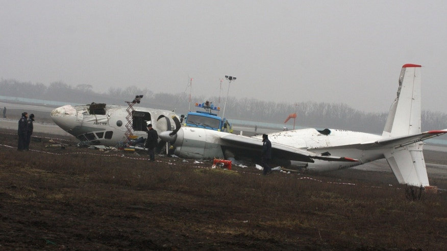 Ukrainian AN-24 plane lies off a runway after it crashed in the eastern Ukrainian city of Donetsk, Thursday, Feb. 14, 2013. A passenger plane carrying soccer fans headed for a match between Shakhtar and Borussia Dortmund, skidded past the landing strip and overturned on Wednesday, killing five people, officials said. The plane was carrying 44 passengers and crew  from the Black Sea port of Odessa when it crash-landed. (AP Photo/Irina Gorbaseva)