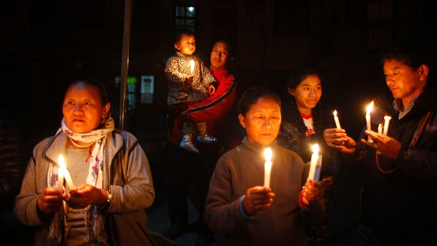 Exile Tibetans participate in a candle light vigil in solidarity with fellow Tibetans who have self immolated, in Katmandu, Nepal, Wednesday, Feb.13, 2013. A Tibetan protester doused himself with gasoline, set himself ablaze and chanted anti-China slogans as he ran down a street in Nepal's capital Wednesday, the latest in a string of self-immolations protesting China's rule over Tibet. (AP Photo/Niranjan Shrestha)