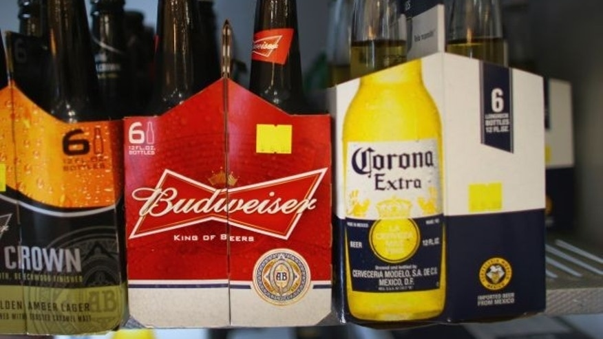 MIAMI, FL - JANUARY 31:  Six packs of Anheuser-Busch's Budweiser and Grupo Modelo's Corona Extra beers sit on a shelf at the Chandi Wine and spirits store on January 31, 2013 in Miami, Florida. Federal authorities filed a lawsuit January 31, to stop the Anheuser-Busch InBev's $20.1 billion takeover of Grupo Modelo.  (Photo Illustration by Joe Raedle/Getty Images)