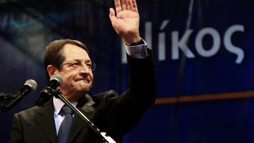 Right-wing presidential candidate Nicos Anastasiades waves to his supporters before his speech during a rally in capital Nicosia, Cyprus, Wednesday, Feb. 13, 2013. Opinion polls a week before Cyprus' presidential election show right-wing presidential candidate Nicos Anastasiades consolidating his substantial lead over his two main rivals. Cyprus presidential elections will take place on Sunday, Feb. 17, 2013. (AP Photo/Petros Karadjias)