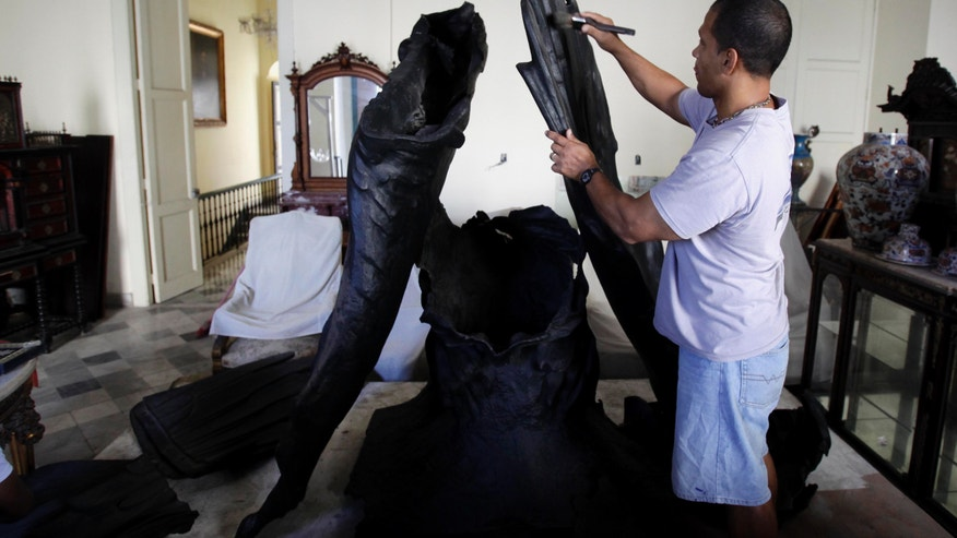 """In this Wednesday, Feb. 13, 2013 photo, a man works to restore the body of an eagle that was torn down from the Maine monument after the triumph of the revolution, at the History of the City Museum in Havana, Cuba. Following the doomed, U.S.-backed Bay of Pigs invasion, the more than 3-ton eagle was ripped from the USS Main monument during an anti-American protest and splintered into pieces. """"I have been the faithful custodian of the body,"""" City Historian Eusebio Leal, told The Associated Press. (AP Photo/Franklin Reyes)"""