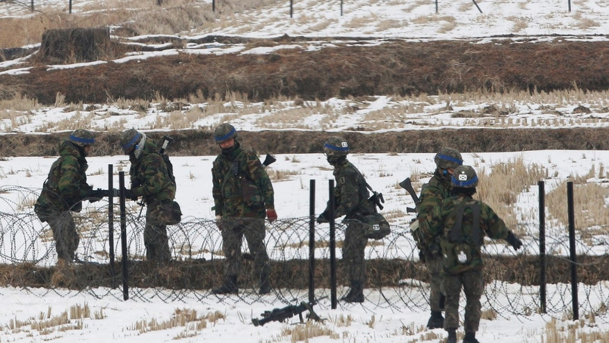 South Korean army soldiers set up barbed wire fence during an exercise near the demilitarized zone of Panmunjom in Paju, South Korea, Thursday, Feb. 14, 2013. North Korea's neighbors bolstered their military preparations and mobilized scientists Wednesday to determine whether Pyongyang's third nuclear test, conducted in defiance of U.N. warnings, was as successful as the North claimed. (AP Photo/Ahn Young-joon)