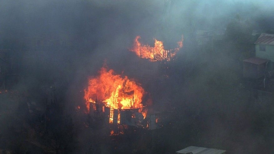Houses burn during a fire at the San Roque hill in Valparaiso, some 75 miles (120 km) northeast of Santiago, Chile, Thursday, Feb. 14, 2013. A forest fire that engulfed a hill in the Chilean port city of Valparaiso destroyed at least 70 homes and forced the evacuation of more than 500 families, officials said on Thursday. (AP Photo/Genaro Morales) CHILE OUT - DO NOT USE IN CHILE - NO USAR EN CHILE