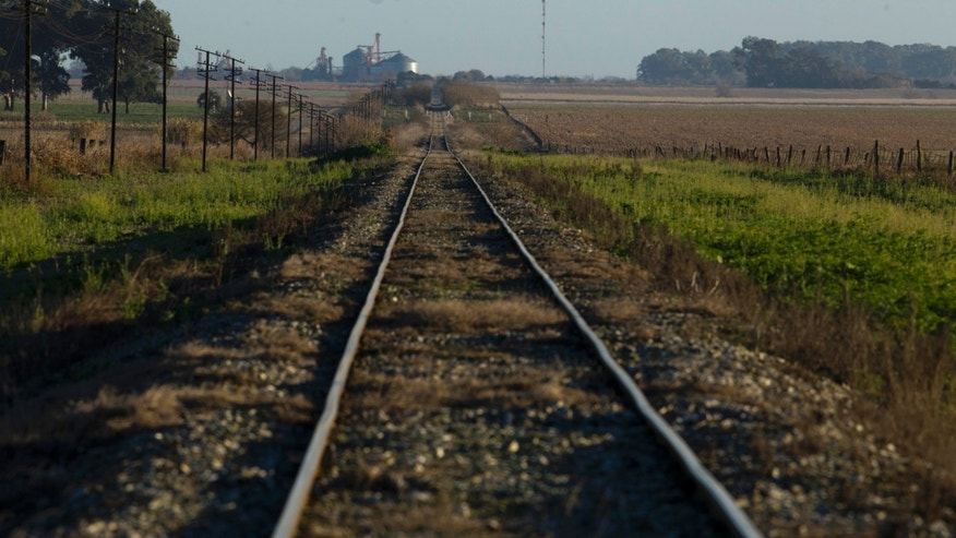 In this July 14, 2012 photo, train tracks cross a farm near Pergamino, Argentina. China agreed to cooperate in financing the modernization of the Belgrano Cargas railway, which connects Argentina capital Buenos Aires with 13 of Argentina's 23 provinces, including the main soybean producing areas  in the north of the country. China is a leading buyer of Argentine soybeans. China has emerged in recent years as the largest provider of development loans to Argentina, Venezuela and Ecuador, according to the Gallagher report. (AP Photo/Natacha Pisarenko)