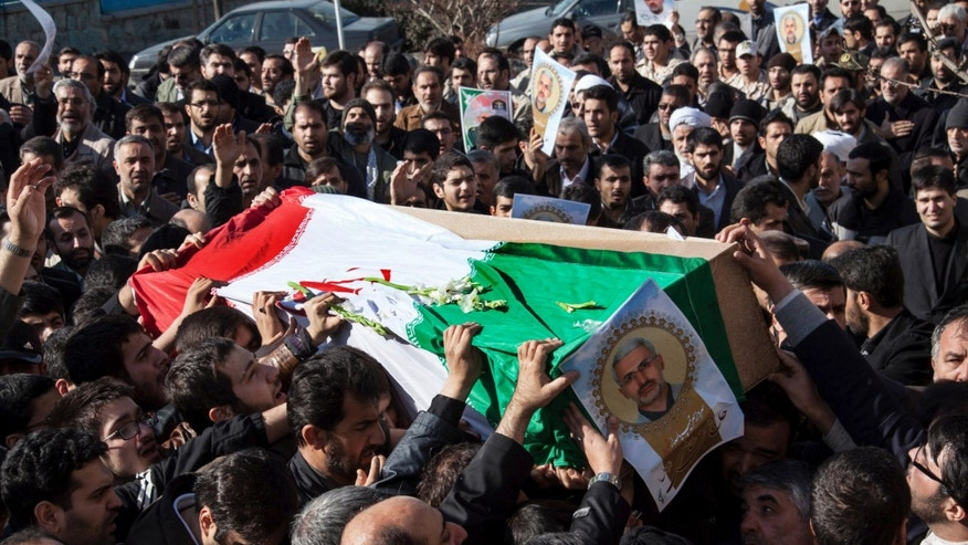 Iranian mourners carry the flag draped coffin of Gen. Hassan Shateri, shown in the poster, in Tehran, Iran, Thursday, Feb. 14, 2013. Prominent Iranian politicians and clerics led mourners at a funeral Thursday for a senior commander of the country's powerful Revolutionary Guards who was killed this week while traveling from Syria to Lebanon, local media said. (AP Photo/Fars News Agency, Saeed Kariminejad)