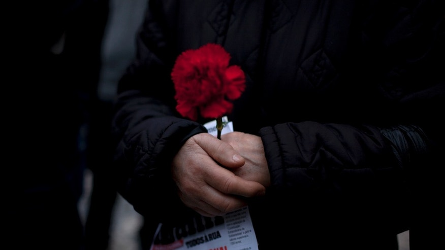 """A woman holds a red carnation and a leaflet with the words """"national shame"""" during an anti-austerity protest march in Lisbon Saturday, Feb. 16 2013. The red carnation is the symbol of the April 25 1974 revolution that restored democracy in Portugal. The protest was called by CGTP, the Portuguese confederation of workers unions. (AP Photo/Armando Franca)"""