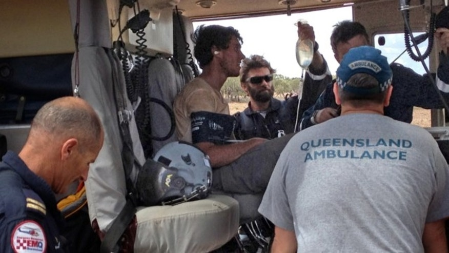 Feb. 15, 2013: British backpacker Sam Derry-Woodhead, second left, sits in a rescue helicopter as he is tended to by ambulance personnel, outside of Longreach, Australia.