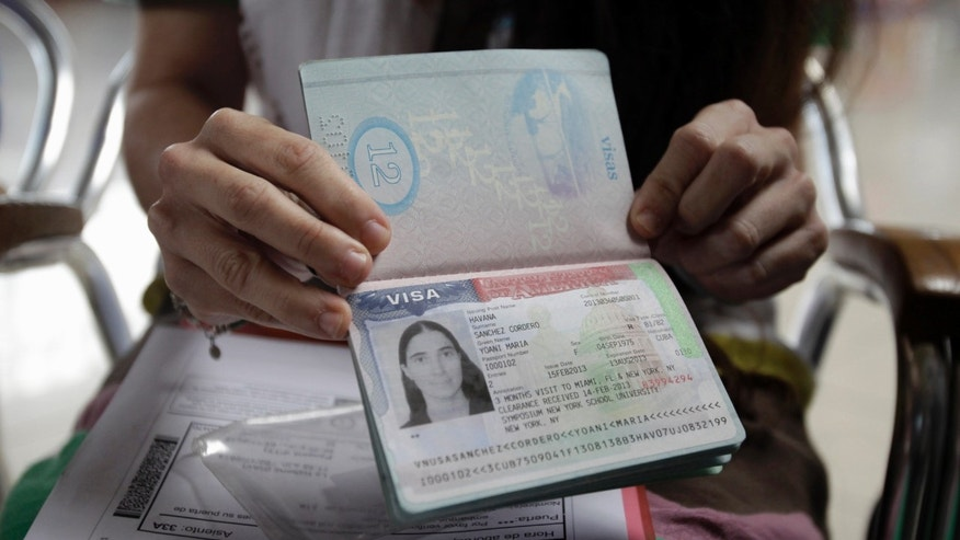 Cuban dissident blogger Yoani Sanchez shows her passport before leaving Cuba to travel to Brazil and other countries at the Jose Marti International Airport in Havana, Cuba, Sunday, Feb. 17, 2013. Sanchez is one of the Cuban dissidents who applied for passports to go overseas under recently enacted travel reform. Her request was granted last month. By her own account Sanchez has on some 20 occasions been rejected for the exit visa that for decades was required of all islanders seeking to go abroad.(AP Photo/Franklin Reyes)