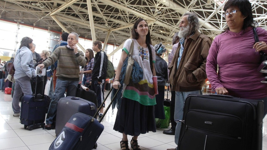 Cuban dissident blogger Yoani Sanchez waits in line to have her documents checked at passport control before leaving Cuba to travel to Brazil and other countries at the Jose Marti International Airport in Havana, Cuba, Sunday, Feb. 17, 2013. Sanchez is one of the Cuban dissidents who applied for passports to go overseas under recently enacted travel reform. Her request was granted last month. By her own account Sanchez has on some 20 occasions been rejected for the exit visa that for decades was required of all islanders seeking to go abroad.(AP Photo/Franklin Reyes)