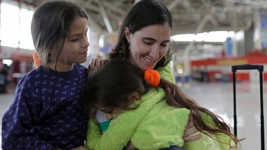 Cuban dissident blogger Yoani Sanchez, left, bids farewell to her nieces Yilianis, left, and Elianis Diaz, before leaving Cuba to travel to Brazil and other countries at the Jose Marti International Airport in Havana, Cuba, Sunday, Feb. 17, 2013. Sanchez is one of the Cuban dissidents who applied for passports to go overseas under recently enacted travel reform. Her request was granted last month. By her own account Sanchez has on some 20 occasions been rejected for the exit visa that for decades was required of all islanders seeking to go abroad.(AP Photo/Franklin Reyes)