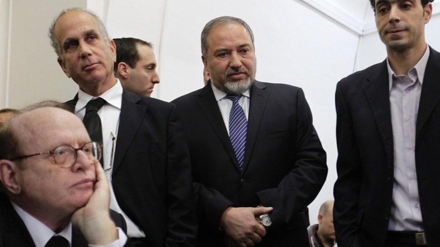 Israel's former hard-line Foreign Minister Avigdor Lieberman, second right, is seen with lawyers and aides as he arrives at a Jerusalem court for the opening hearing of his trial on charges of fraud and breach of trust, Sunday, Feb. 17, 2013. Lieberman is accused of trying to advance the career of a former diplomat who relayed information to him about a since-closed criminal investigation into his business dealings. (AP Photo/Ariel Schalit)