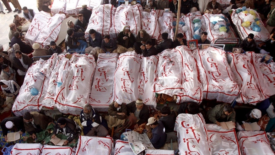 "Feb. 18, 2013 -Protesters have refused to bury victims of the attack until authorities take action against the militants who were responsible. Writing on shrouds reads, ""We are ready Hussain."""