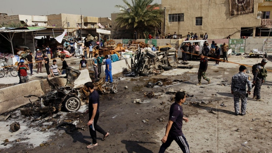 Feb. 17, 2013 - Iraqis inspect the scene of a car bomb attack in the Ameen neighborhood in eastern Baghdad, Iraq.