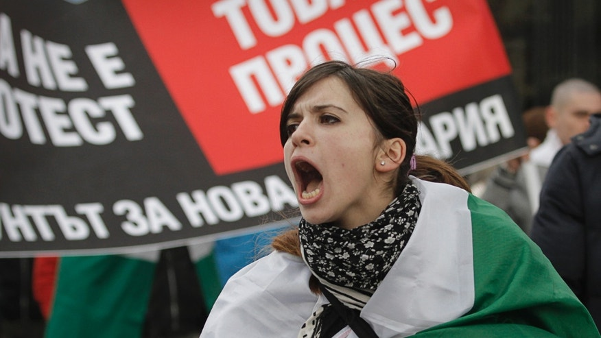 "A Bulgarian woman shout slogans during a protest against higher electricity and heating bills, in Sofia,  Sunday, Feb. 17, 2013. Thousands of angry Bulgarians chanted ""mafia"" and ""resignation""  demanded the expulsion of the three foreign-controlled power distributors that control the local market: Czech Republic's CEZ and Energo-Pro, and Austria's EVN   (AP Photo/Valentina Petrova)"