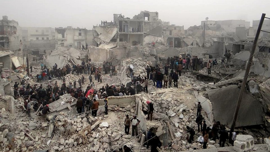 Feb. 19, 2013: This citizen journalism image provided by Aleppo Media Center AMC, which has been authenticated based on its contents and other AP reporting, shows people searching through the debris of destroyed buildings in the aftermath of a strike by Syrian government forces, in the neighborhood of Jabal Bedro, Aleppo, Syria.