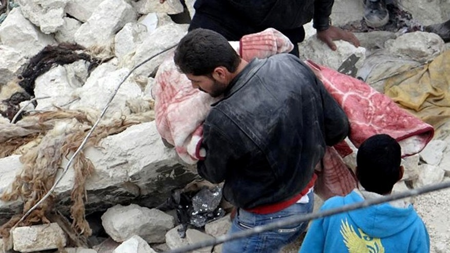 Feb. 19, 2013: This citizen journalism image provided by Aleppo Media Center AMC which has been authenticated based on its contents and other AP reporting, shows a Syrian man carrying a child's body in the aftermath of a strike by Syrian government, in the neighborhood of Jabal Bedro, in Aleppo, Syria.