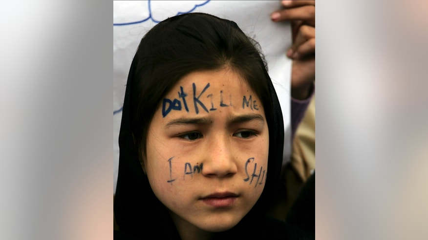 "A Pakistani Shiite girl takes part in a sit-in protest with others to condemn the Saturday bombing which killed scores of people, in Quetta, Pakistan on Monday, Feb. 18, 2013. The families of the bombing victims have refused to bury their loved ones until authorities take action against the militants who were responsible. Mispelled and partially shown writing reads, ""don't kill me. I am Shia."" (AP Photo/Arshad Butt)"