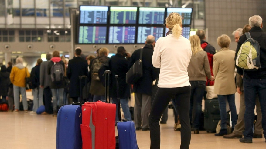 A woman waits as passengers queue at the security check at the airport in Hamburg, Germany, Thursday, Feb. 14, 2013. Hundreds of flights have been canceled after security personnel walked off the job at two German airports in a dispute over wages. Security workers at Duesseldorf and Hamburg airports started the one-day warning strike at 4 a.m. Thursday after wage negotiations failed to make any progress. (AP Photo/dpa, Malte Christians)