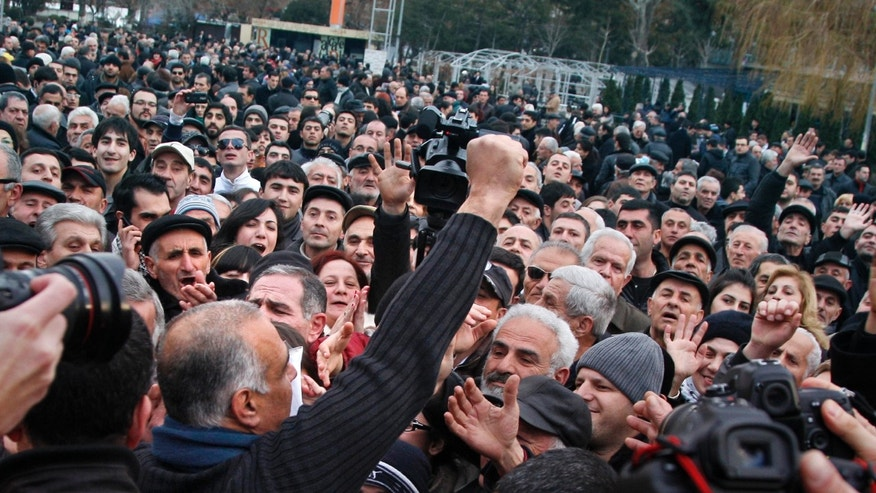 Presidential candidate Raffi Hovanessian, front, gestures at a rally in Yerevan, Armenia, Tuesday, Feb. 19, 2013. American-born Raffi Hovanessian, Armenia's first foreign minister after the 1991 collapse of the Soviet Union, on Tuesday called the election unfair and rigged, claiming cases of ballot-box stuffing and voters being coerced to back Armenia's President Serge Sarkisian. Armenia's president easily won a second term, according to preliminary election results Tuesday. At a protest rally in the capital that drew 2,000-3,000 people, Hovanessian declared himself the genuine winner and called on Sarkisian to arrange a transfer of power by Wednesday evening.  (AP Photo/PanARMENIAN, Tigran Mehrabyan)