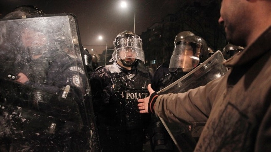 Feb. 19, 2013: A protester reaches his hand out to a riot police officer after clashes with demonstrators in a protest against high electricity prices in Sofia.