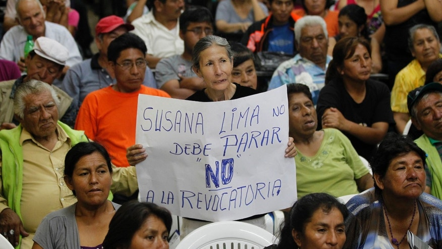 "In this Feb. 8, 2013 photo, a supporter of Lima's Mayor Susana Villaran holds a sign that reads in Spanish ""Susana, Lima, should not stop, no to the recall"" at a meeting between Villaran and newspaper vendors in Lima, Peru. Villaran, a 63-year-old career human rights defender and the first woman ever elected to manage Peru's capital, is fighting for her political life in a March 17 recall election that she says was organized by the very power brokers she has disenfranchised. (AP Photo/Martin Mejia)"