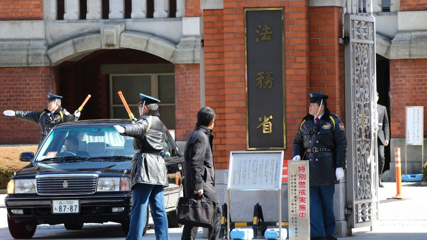 Security guards stand at the entrance to the Justice Ministry in Tokyo Thursday, Feb. 21, 2013. The ministry said Japan executed early Thursday three inmates convicted of murder in its first executions under the government that took office in December. Executions in the country are done by hanging. (AP Photo/Koji Sasahara)