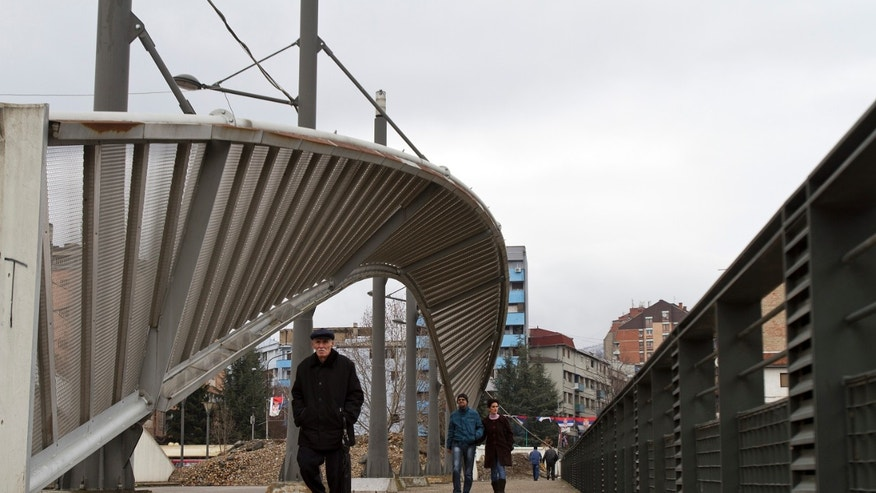 An elderly Kosovo man and a couple cross the bridge in Mitrovica that splits the city into the Serb run north and ethnic Albanian south on Thursday, Feb. 19, 2013. Kosovo officials say a series of hand grenade attacks in Kosovo's north are aimed at derailing efforts to bring the lawless area under control. Some twenty attacks have been registered in the last two months in the tense town of Mitrovica, split between Serbs and ethnic Albanians. ( AP Photo / Visar Kryeziu )