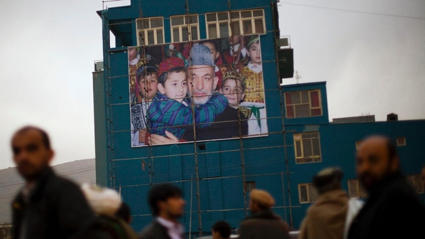 FILE - In this Nov 22, 2009, file photo, Afghan men waiting to get a ride out of the city queue next to a giant poster of Afghanistan's President Hamid Karzai in Kabul, Afghanistan. At least half the Afghan Taliban recently freed from Pakistani prisons have rejoined the insurgency, a Pakistani intelligence official said, complicating further releases and throwing into question the value of such goodwill gestures to restart a flagging peace process that shows no sign of ending a war that has raged for more than 11 years. (AP Photo/Anja Niedringhaus, File)