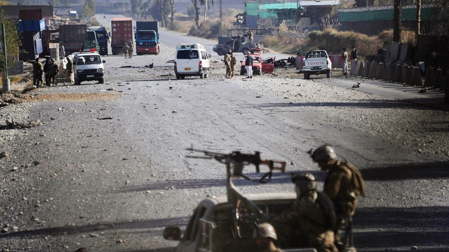 FILE - In this Dec. 2, 2012 file picture, Afghan security forces block the road where Taliban suicide bombers attacked a joint U.S.-Afghan air base in Jalalabad, east of Kabul, Afghanistan. At least half the Afghan Taliban recently freed from Pakistani prisons have rejoined the insurgency, a Pakistani intelligence official said, complicating further releases and throwing into question the value of such goodwill gestures to restart a flagging peace process that shows no sign of ending a war that has raged for more than 11 years.  (AP Photo/Nasrullah Khan, File)