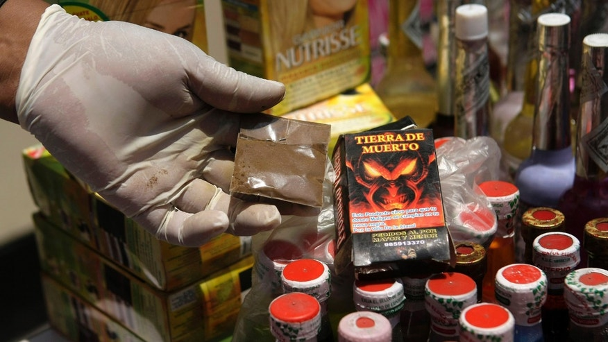 "A municipal pharmaceutical chemist shows a product called Spanish ""Soil of death,"" one of many products seized from faith healers in Lima, Peru, Thursday, Feb. 21, 2013. City enforcement officials say the supposed elixirs confiscated in a raid are of dubious and unlicensed provenance and that shop owners will be prosecuted for public health crimes carrying penalties of up to 10 years in prison. (AP Photo/Karel Navarro)"