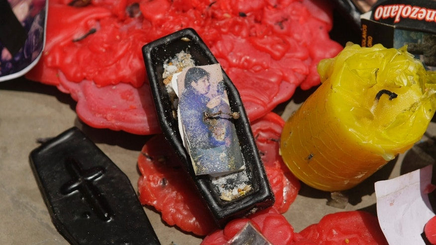 "A miniature coffin containing a photo stuck with a pin sits among other products seized from faith healers in Lima, Peru, Thursday, Feb. 21, 2013. City enforcement officials say the supposed elixirs confiscated in a raid are of dubious and unlicensed provenance and that shop owners will be prosecuted for public health crimes carrying penalties of up to 10 years in prison. One potion of note purported to protect ""against damages and scares."" Another was destined to ""bring your rival to his knees."" (AP Photo/Karel Navarro)"