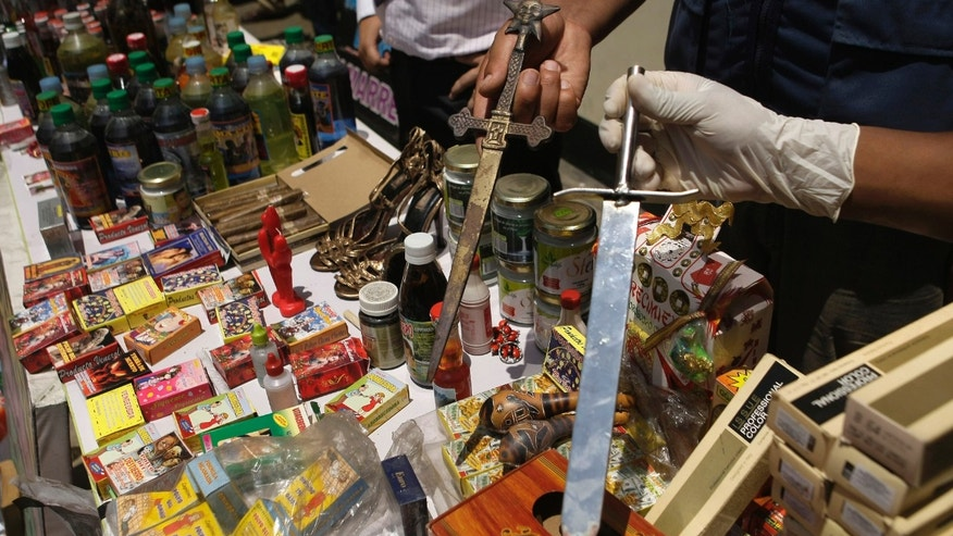 "City officials display seized swords among other products confiscated from faith healers in Lima, Peru, Thursday, Feb. 21, 2013. City enforcement officials say the supposed elixirs confiscated in a raid are of dubious and unlicensed provenance and that shop owners will be prosecuted for public health crimes carrying penalties of up to 10 years in prison. One potion of note purported to protect ""against damages and scares."" Another was destined to ""bring your rival to his knees."" (AP Photo/Karel Navarro)"