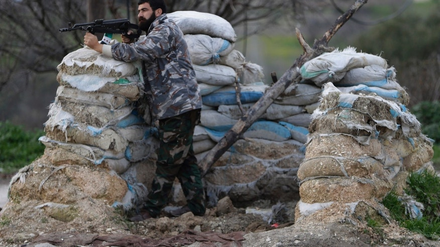 Feb. 21, 2013 - Free Syrian Army fighter takes his position at a previous Syrian army forces checkpoint, at the main entrance of Christian village of Yacoubieh, in the northern Syrian province of Idlib, Syria.