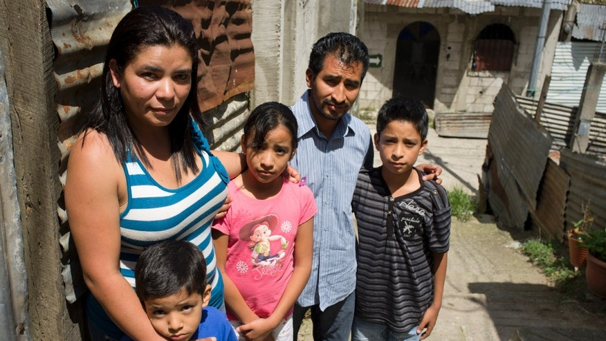 In this photo taken on Sunday, Oct. 7, 2012, Gregoria Herminia Contreras, 35, poses for a photo with her husband Filadelfo Julián Ramos, and their children; Daniel, right,  Estefany, center, and Jeffry, left, in Guatemala City. Contreras was four years old when she was separated from her parents by a Salvadoran soldier, who then registered her under a new name and forcibly adopted her during the country's civil war. The non-governmental agency Pro Búsqueda and the National Search Commission for Missing Children say they have documented at least ten cases of missing children who were abducted by Salvadoran military to raise as their own or to offer them for adoption in exchange for money. The agencies believe case numbers would be much higher if the military disclosed their national security archives. (AP Photo/Moises Castillo)
