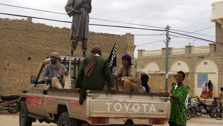 Aug. 31, 2012: In this file photo, fighters from the Al Qaeda-linked Islamist group Ansar Dine stand guard in Timbuktu, Mali, as they prepare to publicly lash a member of the Islamic Police found guilty of adultery.